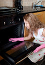 Young woman cleaning the oven Stock Photo