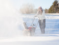 Young woman clearing drive with snowblower lady using a on rural on windy day a cloud or blizzard of snow blowing in the air and Royalty Free Stock Image