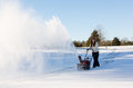 Young woman clearing drive with snowblower lady using a on rural on windy day a cloud or blizzard of snow blowing in the air Royalty Free Stock Photo
