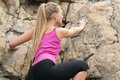 Young woman climbing on the rock image of blonde lady fitness training Royalty Free Stock Photos