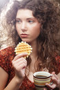 Young woman with coffee and cookies Royalty Free Stock Photo