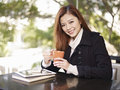 Young woman in coffee shop asian adult holding cup looking at camera smiling cafe Stock Image