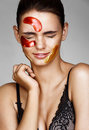 Young  woman with color patches on her face screwed up her eyes. Royalty Free Stock Photo