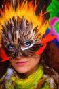 Young woman with a colorful feather carnival face mask on bright colorful background, eye contact, make up artist. Royalty Free Stock Photo
