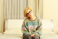 Young woman in colourful sweater sitting on the bed Royalty Free Stock Photo