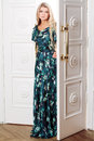 Young woman comes out of the door in a long dress Royalty Free Stock Image