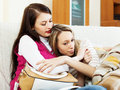 Young woman comforting crying friend women at sofa in home Royalty Free Stock Photography