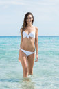 Young woman comming out of the caribbean refreshing water happy in white bikini standing at tropical beach Stock Photos