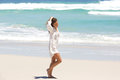 Young woman in contemplation walking on the beach Royalty Free Stock Photo