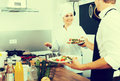Young woman cook giving salad to waitress Royalty Free Stock Photo