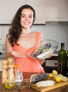 Young woman cooking fresh fish  in frying pan Royalty Free Stock Photo