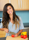 Young woman cooking healthy food at home perparing vegetables for salad lifestyle concept Royalty Free Stock Photo