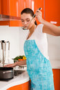 Young woman cooking in the kitchen, tasting soup Royalty Free Stock Image
