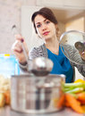 Young woman cooking soup with laddle veggie in kitchen at home Royalty Free Stock Photos