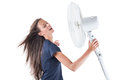 Young woman cooling herself under wind of cooler fan isolated on white background Royalty Free Stock Photo