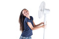 Young woman cooling herself under wind of cooler fan isolated on white background. Royalty Free Stock Photo
