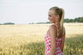 Young woman in a corn field summer dress standing cornfield she looks relaxed and cheerful Royalty Free Stock Images
