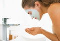 Young woman with cosmetic mask on face washing in bathroom Royalty Free Stock Images