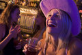 Young woman in cowboy hat laughing at a nightclub Stock Image