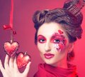 Young woman with creative make up red and pink hearts Stock Photo