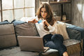 Young woman with credit card using laptop in loft Royalty Free Stock Photo