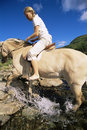Young woman crossing a river by horse Royalty Free Stock Image