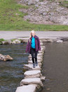 Young woman crossing stepping stones sovedale Royalty Free Stock Photo