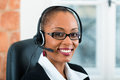 Young woman from the customer service businesswoman or secretary working in her office with a headset she has a pitch Stock Photography