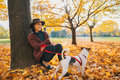 Young woman with cute dog sitting under tree in autumn park portrait of Royalty Free Stock Image