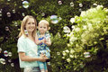 Young woman with daughter girl in her arms walks women the summer among soap bubbles Royalty Free Stock Image
