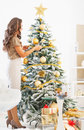 Young woman decorating christmas tree with christmas ball full length portrait of Stock Photo