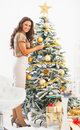 Young woman decorating christmas tree with christmas ball full length portrait of happy Stock Images