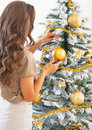 Young woman decorating christmas tree with christmas ball rear view Royalty Free Stock Photo