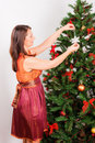 Young  woman decorating  a fir-tree Royalty Free Stock Photography