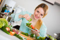 Young woman decorating salad with herbs in kitchen