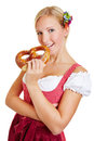 Young woman in dirndl biting in pretzel happy smiling a a Royalty Free Stock Photo
