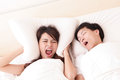 Young woman disturbed by the snores of her husband women in bedroom at home asian family Stock Images