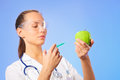 Young woman doctor injecting green apple Stock Photos