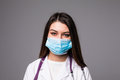Young woman doctor or nurse in cap and face mask on grey Royalty Free Stock Photo