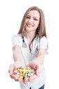 Young woman doctor offering pills holding and many with both hands Royalty Free Stock Photo
