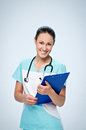 Young woman doctor in scrubs with a black pediatric stethoscope holding blue tablet for papers. Royalty Free Stock Photo