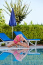 Young woman does exercises for flexibility on poolside Stock Image