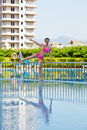 Young woman does morning exercises on poolside holding to handrails Royalty Free Stock Photo