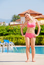 Young woman does shoulder to shoulder head roll smling at poolside Royalty Free Stock Images