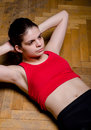 A young woman doing abdominal crunches on a wooden floor Royalty Free Stock Photography
