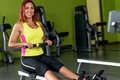 Young woman doing back exercises red haired her muscles on a seated row machine Stock Photo