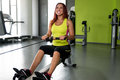 Young woman doing back exercises red haired her muscles on a seated row machine Stock Image