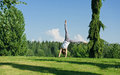 Young woman doing cartwheel outside cheerful in the sunshine Royalty Free Stock Images