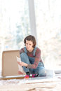 Young woman doing diy renovations competent kneeling working on the floor in her living room in front of large bright windows with Royalty Free Stock Photos