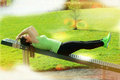 Young woman doing exercise outdoors exercises on a sports device in the park Stock Photos